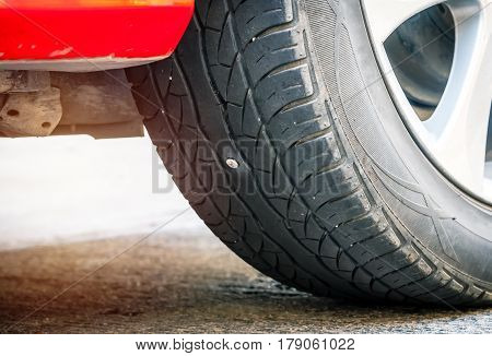 Screw punctured car tire at outdoor day