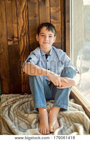 Teenager boy sitting on a wooden window sill