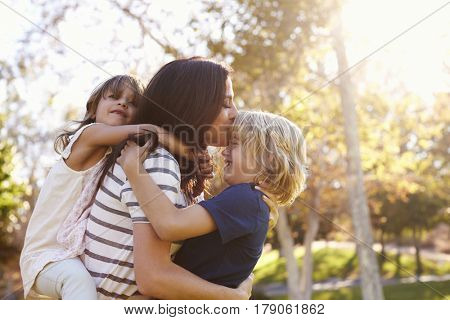 Mother Carrying Son And Daughter As They Play In Park