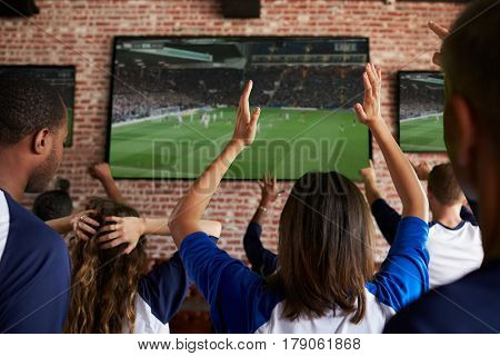 Rear View Of Disappointed Friends Watching Game In Sport Bar