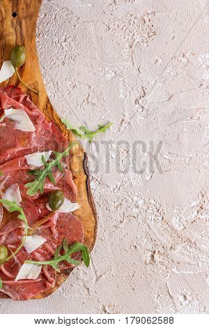 Beef carpaccio on olive wood serving board with capers, olive oil cheese and arugula, served over beige concrete texture background. Top view with space for text.
