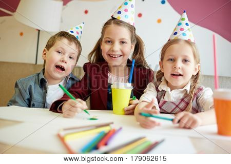 Ecstatic kids drawing at birthday party