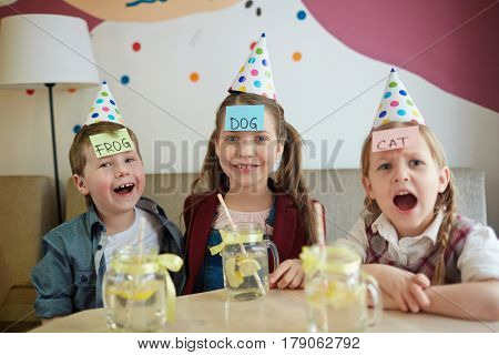 Funny kids playing game with sticky notepapers on foreheads