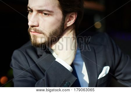 Sunlit head and shoulders portrait of handsome bearded man wearing elegant business suit, looking away frowning and rubbing his neck