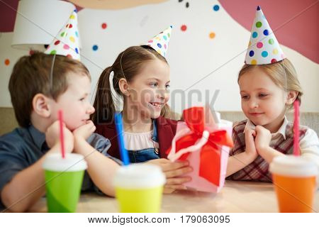 Adorable girl looking at birthday surprise being given by her friend