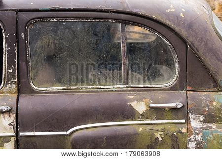 The door is very old car which is under the open sky.