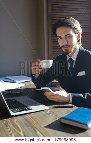 Portrait of handsome elegant businessman working with smartphone and laptop at wooden sunlit table during coffee break, looking at camera and smiling charmingly