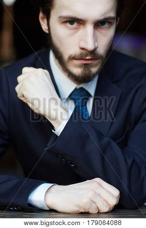 Head and shoulders portrait of handsome bearded man wearing elegant business suit, looking sharply at camera with intimidating hand gesture