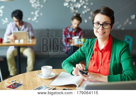 Happy leader of design team holding smartphone over open journal
