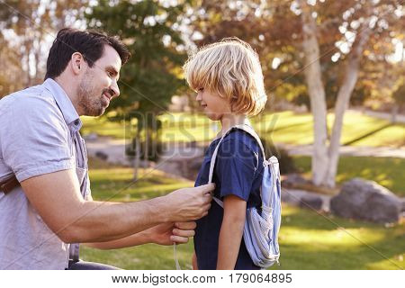 Father Fastening Son's Backpack As They Get Ready For Hike