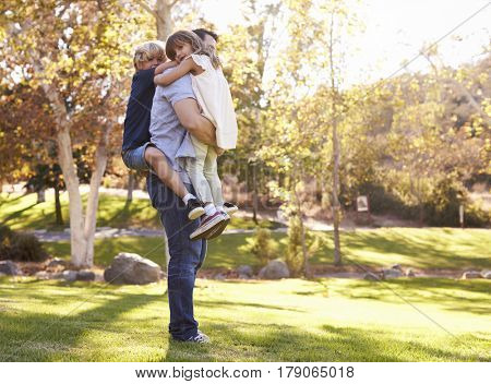 Father Carrying Son And Daughter As They Play In Park
