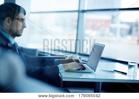 Profile view of concentrated young businessman in eyeglasses sitting at office desk and writing response letter to his partner on modern laptop, view through glass wall