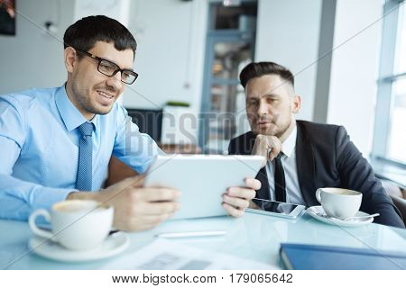 Waist-up portrait of young bearded employee holding digital tablet in hands and presenting his project to colleague, he listening to him with attention