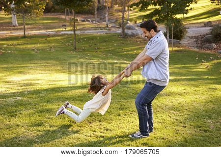 Father Swinging Daughter By Her Arms In Park