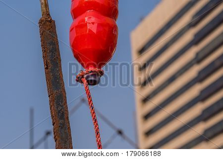 Seoul South Korea March 18 2017: Plastic bottle of red liquid hung from a rusted steel pole with rope extending from the cap to resemble a blood drip
