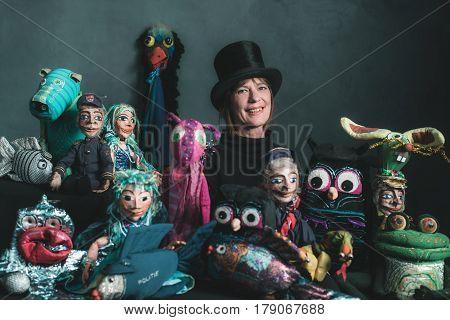 Smiling puppeteer standing between her handmade puppets.