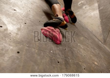 fitness, extreme sport, bouldering, people and healthy lifestyle concept - foot of young woman exercising at indoor climbing gym