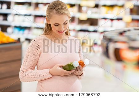 shopping, food, pregnancy, healthy eating and people concept - happy pregnant woman with juice bottles at grocery store or supermarket