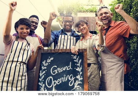 Group of friends with grand opening board together