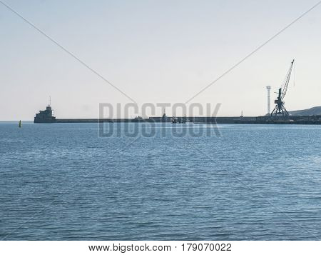The pier and port cranes on the sea background