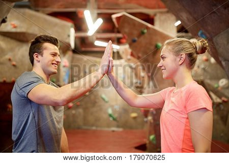fitness, extreme sport, bouldering, people and healthy lifestyle concept - man and woman exercising at indoor climbing gym wall and making high five gesture
