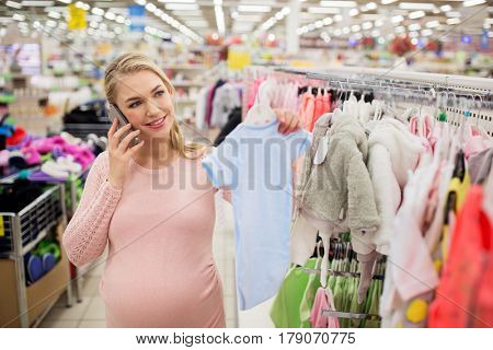 pregnancy, people, technology and shopping concept - happy pregnant woman with blue baby bodysuit calling on smartphone at clothing store