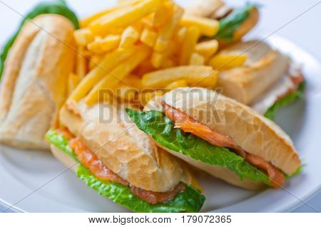 Sandwich With Salmon, Tomato, Cheese And Golden French Fries Potatoes