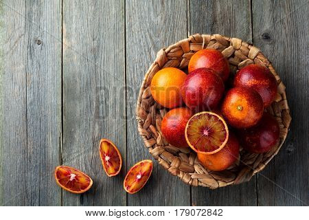 Fresh ripe Sicilian oranges and sliced pieces on a wooden old background. Selective focus. Top view.