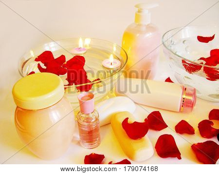 spa bowl with pink water with rose petals and cremes