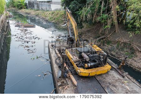 Boat scoop mud dredging the canal in bangkok canal in thailand