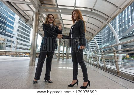 Two asian businesswomen shake hands with in city.