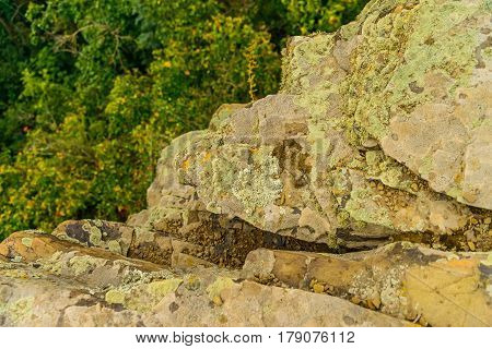 Stone covered by lichen. Natural textured background. Greyrock with cracks and colorful spots of lichen. Spotted yellow and grey abstract pattern with place for your text