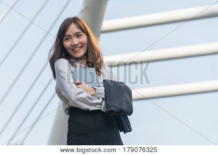 Businesswoman holding tablets and smiled happily in the city.