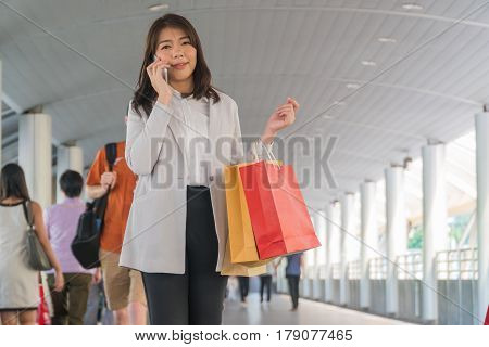 Pretty woman holding shopping bags and talking on cell phone happily with in city.