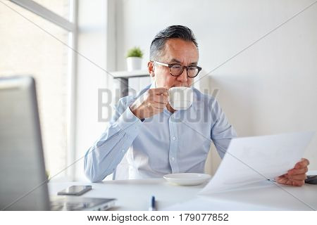 business, people, paperwork and technology concept - businessman reading paper and drinking coffee at office