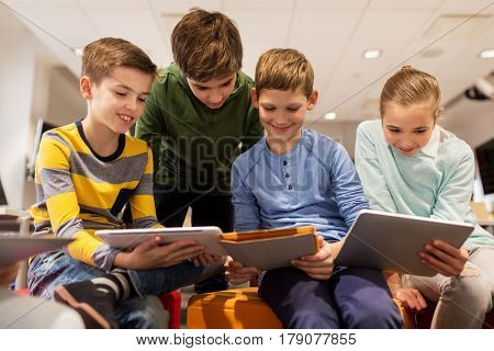 education, children, technology and people concept - group of happy kids with tablet pc computers learning at school