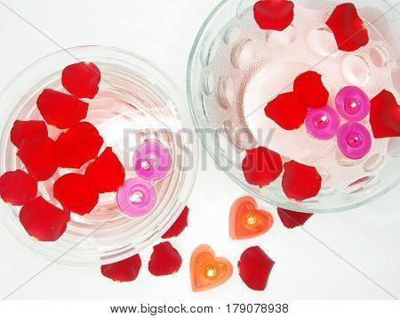 spa floating scented candles among red rose petals