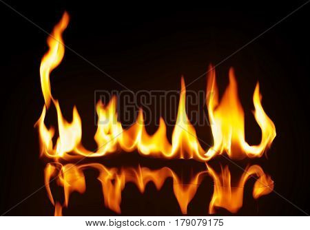 A strip of fire on the reflecting surface. On a black background.