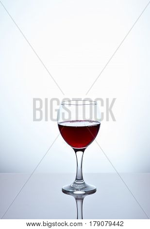 One glass filled with half red wine