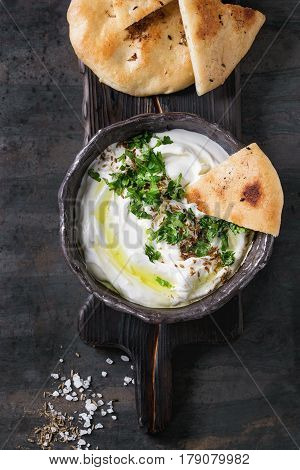 labneh middle eastern lebanese cream cheese dip with olive oil, salt, herbs served traditional pita bread in terracotta bowl over dark texture metal background. Top view with space
