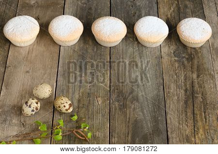 Row of five muffins and quail eggs on an aged wooden background. With space to write a text. Focus is on quail eggs