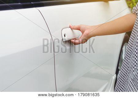 Close up woman hand opening a car door Hand holding door hand to open