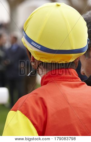Jockey head detail before the race. Hippodrome background. Racehorse. Competition