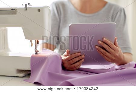 people, needlework, technology and tailoring concept - tailor woman with sewing machine, tablet pc and fabric poster