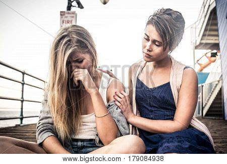 Young woman is sad crying and being consoled by friend