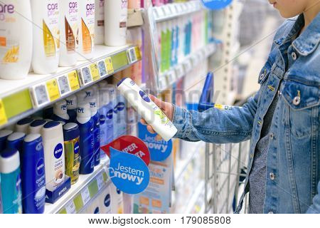 Nowy Sacz Poland - March 29 2017: Young woman in front of aisle with a variety of personal care products of Nivea Company in a Tesco Hypermarket.