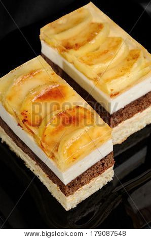 Cake stacked from caramel apple mousse chocolate and almond biscuit with a jelly layer of slices caramelized apple
