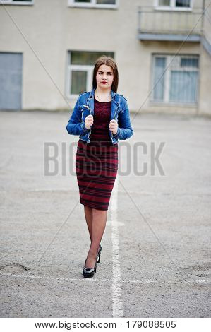 Young Chubby Teenage Girl Wear On Red Dress And Jeans Jacket Posed Against School Backyard.