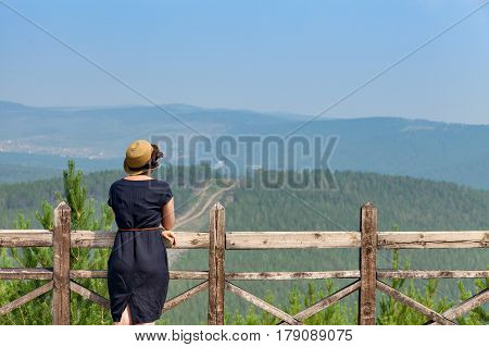 Woman leaning on handrail and looking away on the background of the mountainscape.