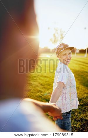 Point of view portrait of a diverse couple in love hanging out in a city parc holding hands at sunset with flare sunlight